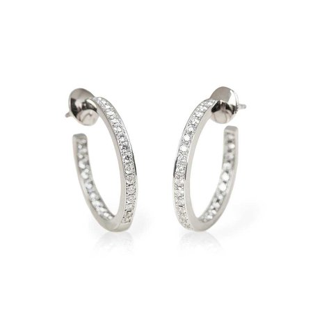 Earrings by Cartier feature round brilliant cut Diamonds