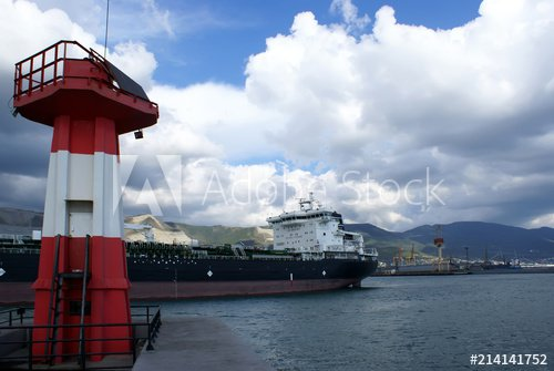 The ship passes near red the lighthouse - Buy this stock photo and explore similar images at Adobe Stock | Adobe Stock