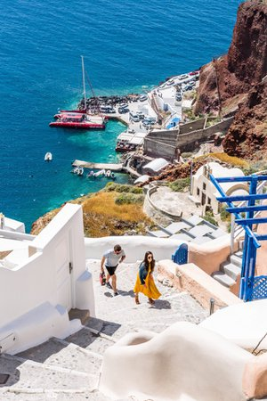 Free stock photo of Couple walking up steep stairs from beautiful blue sea below, Santorini Greece - Reshot
