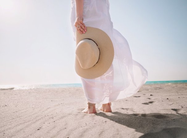 Free stock photo of Portrait of beautiful woman in white dress and hat in hand walking on beach near sea or ocean - Reshot