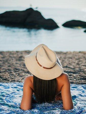 Free stock photo of Girl in hat lying on beach near sea - Reshot