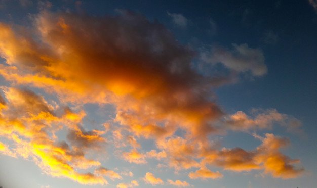 Background with many yellow and orange clouds over blue sky Photo | Premium Download