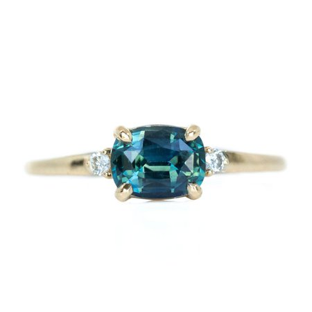 TEAL BLUE THREE STONE RING FEATURING 1.15CT CUSHION SAPPHIRE AND DIAMONDS IN EAST-WEST SETTING by Anueva Jewelry